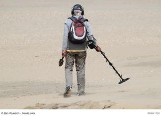 Mann mit Metalldetektor am Strand
